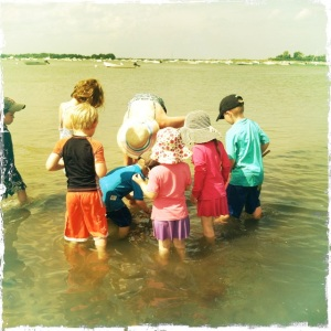 A crowd of kids at the beach with boats and an island in the distance.